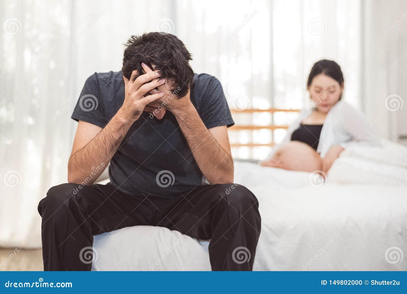 Homem preocupado do esforço que senta-se na cama com mão na testa no quarto na emoção séria do humor com fundo grávido da mulher