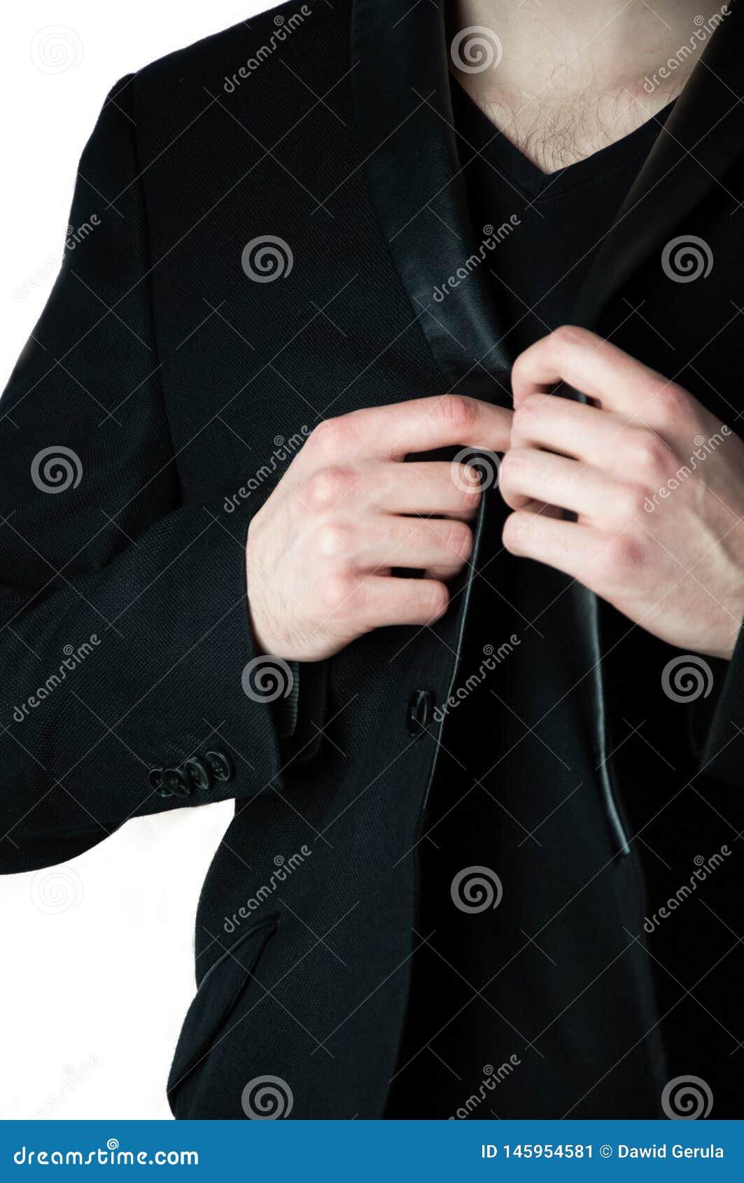 Homem principal colhido no tshirt preto de V que guarda o colar do blazer