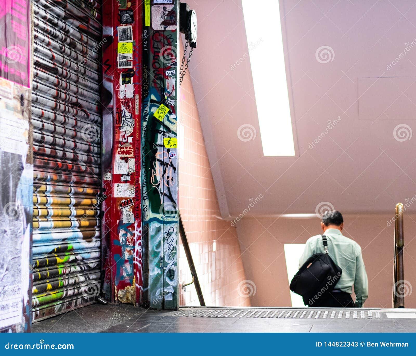 Homem que anda na estação de metro subterrânea