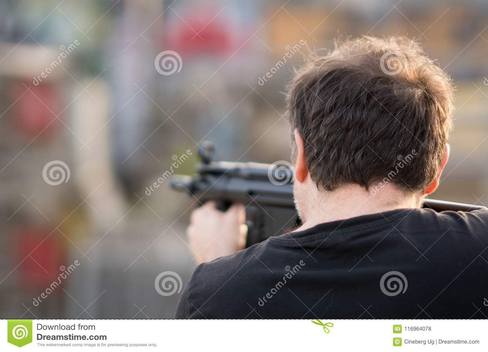 Homem que aponta com um rifle