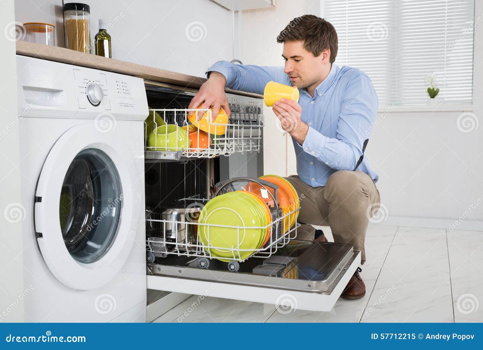 Homem que arranja pratos na máquina de lavar louça