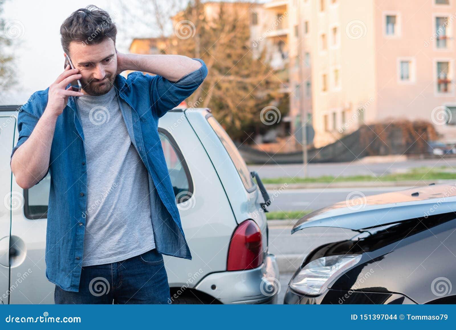 Homem que chama o servi?o da borda da estrada ap?s o acidente de via??o
