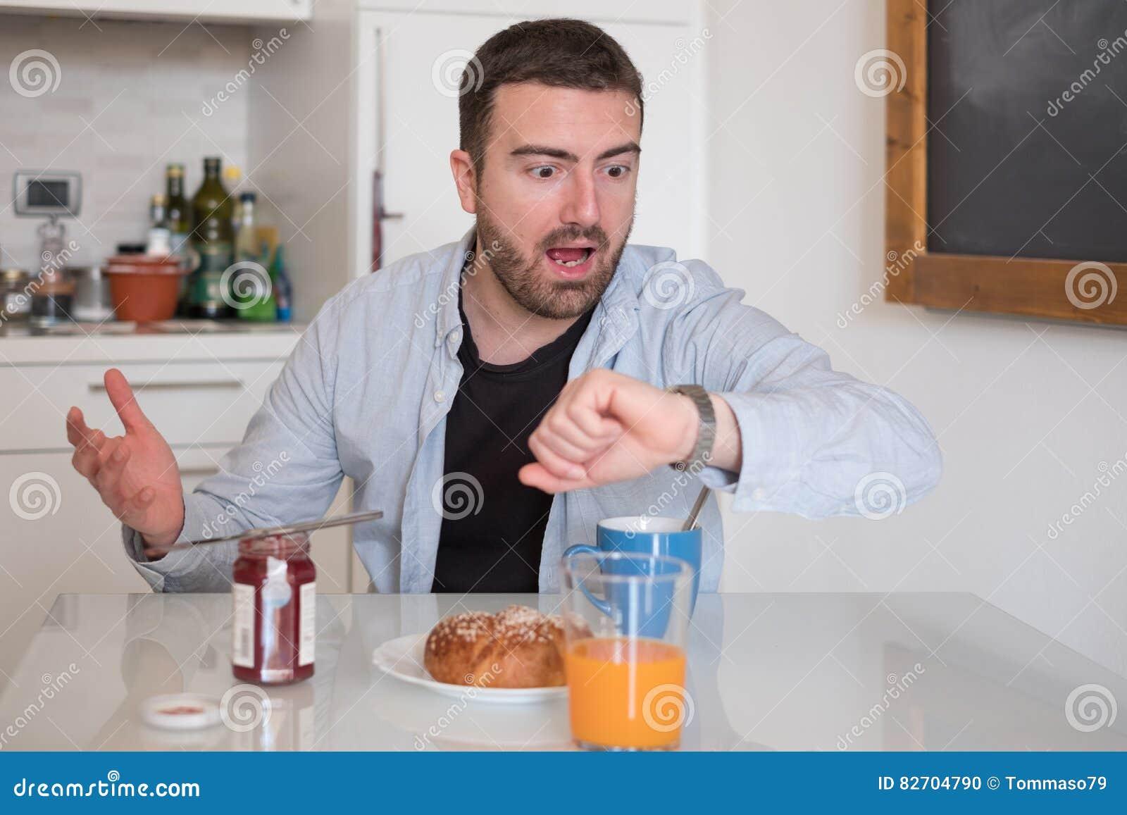 Homem que come o café da manhã mas para ir demasiado tarde trabalhar