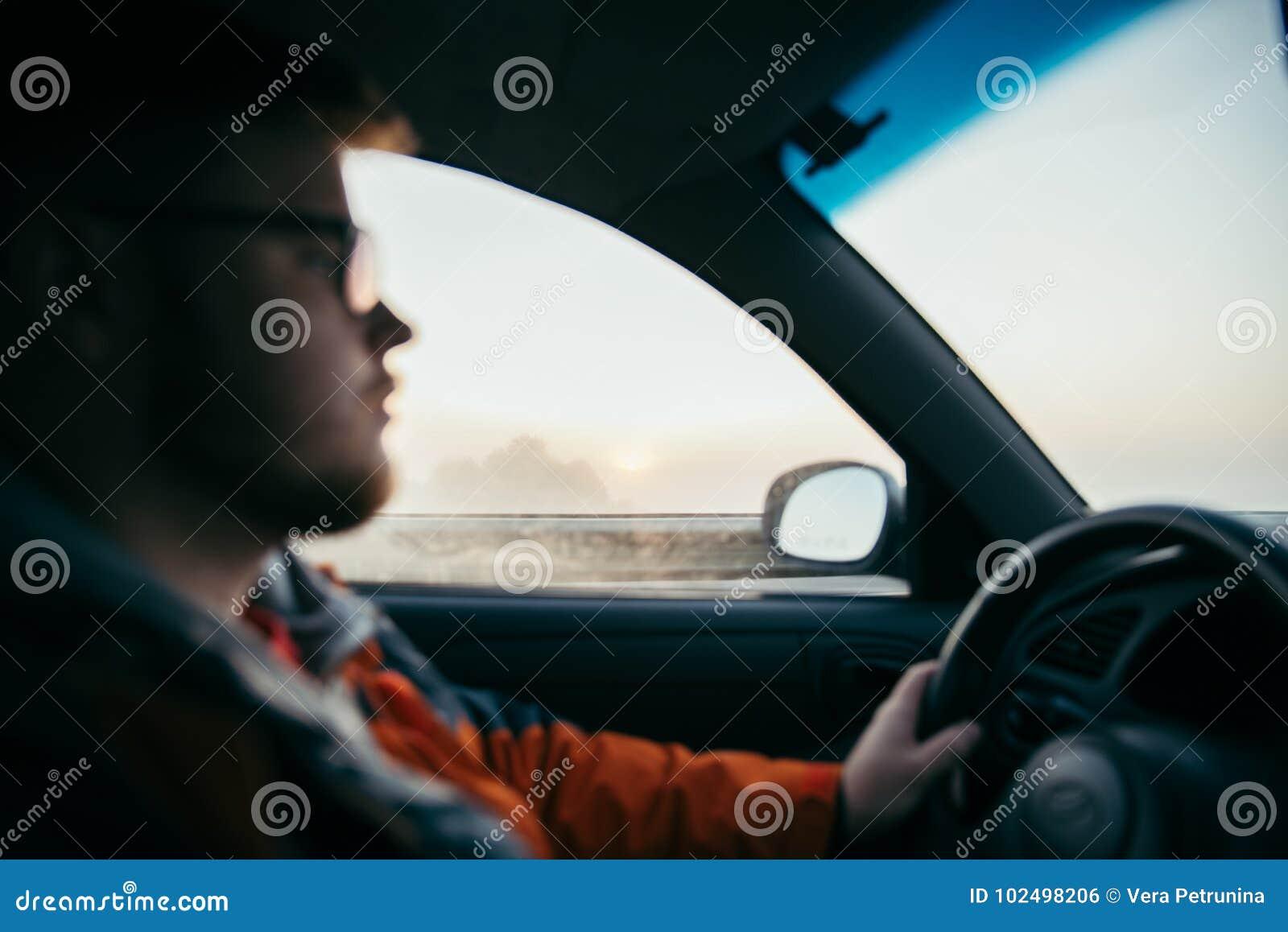 Homem que conduz o carro na névoa