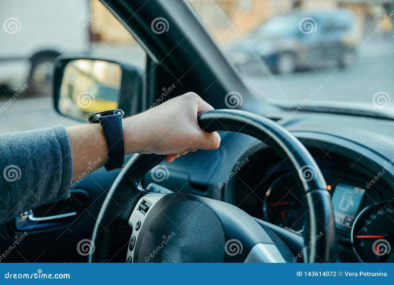 Homem que conduz o carro por ruas da cidade