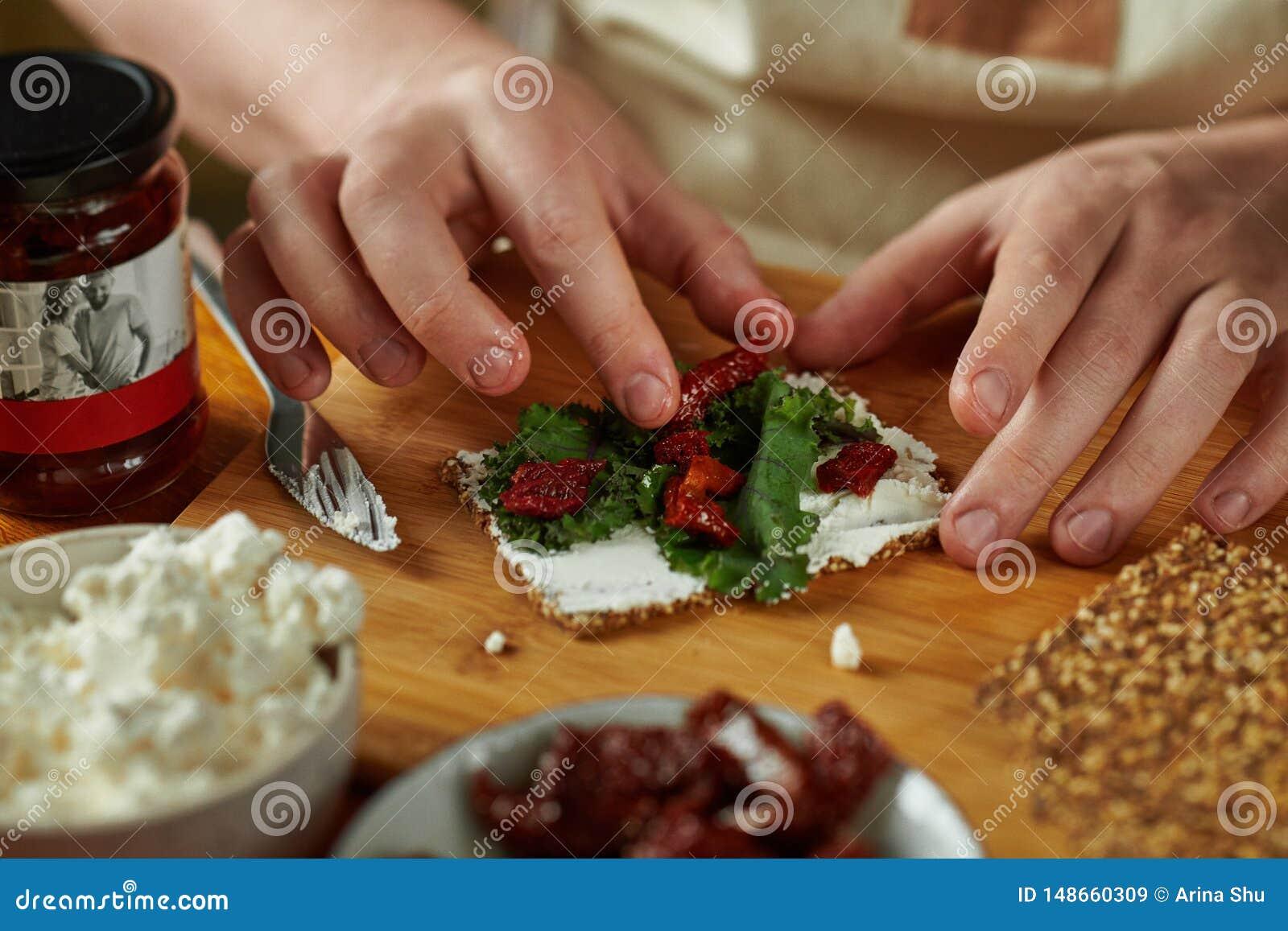 Homem que cozinha o bruschetta, somente m?os no quadro