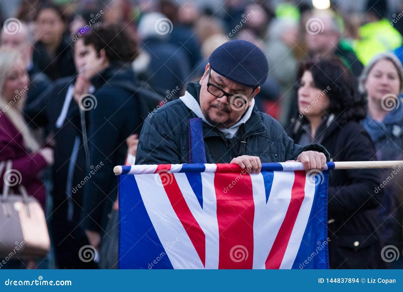 Homem que desdobra a união Jack Flag na multidão de Trafalgar Square