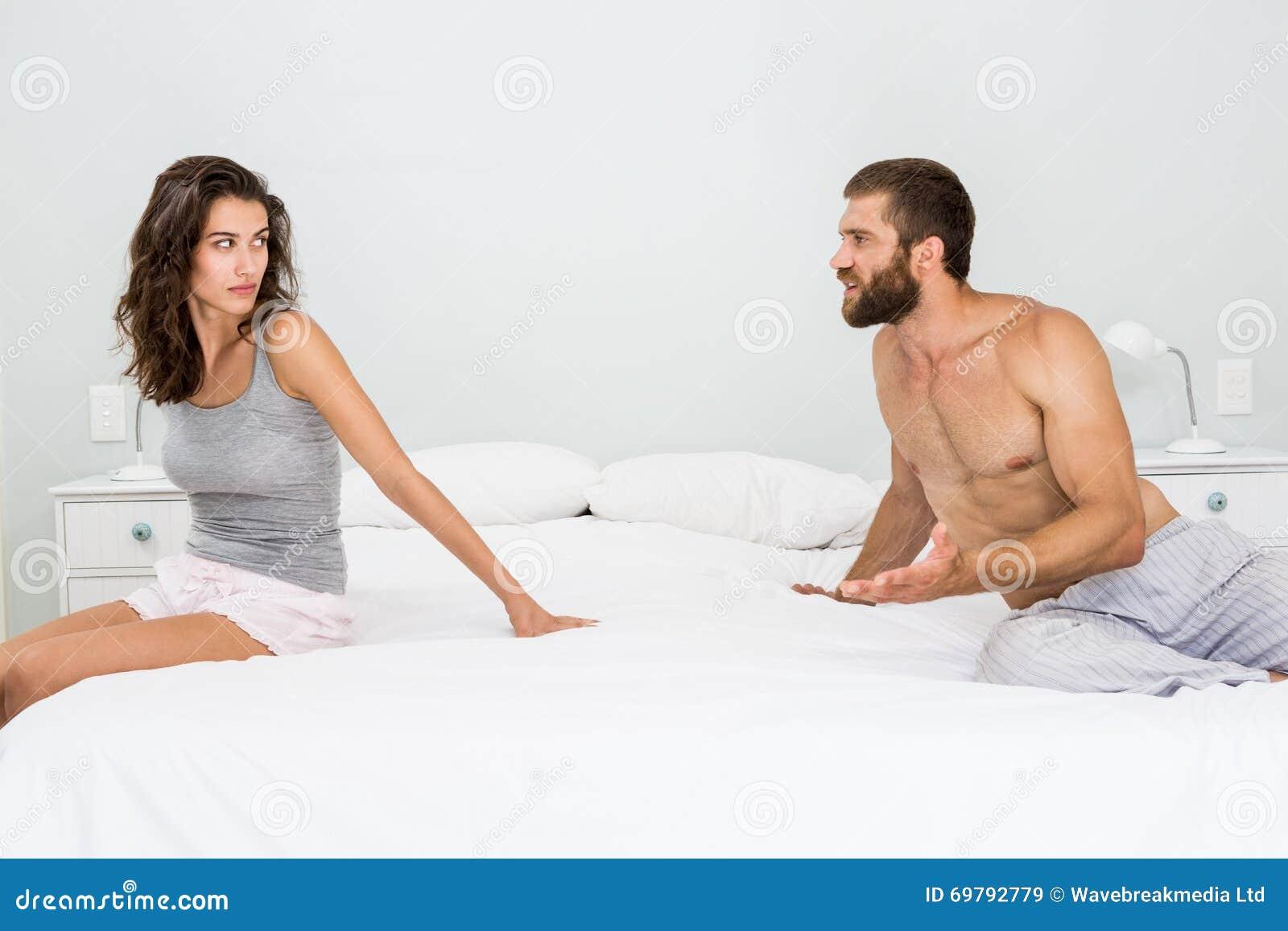Homem que discute com a mulher na cama