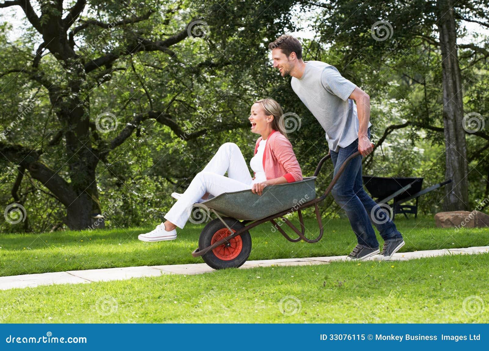 Homem que empurra a mulher no carrinho de mão