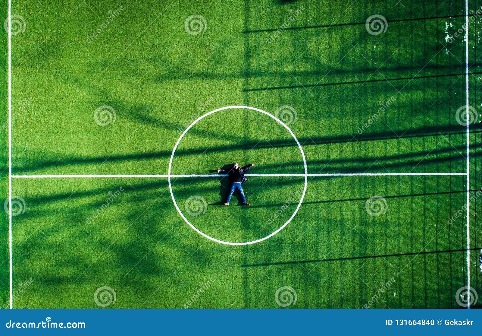 Homem que encontra-se no centro do campo de futebol, vista superior