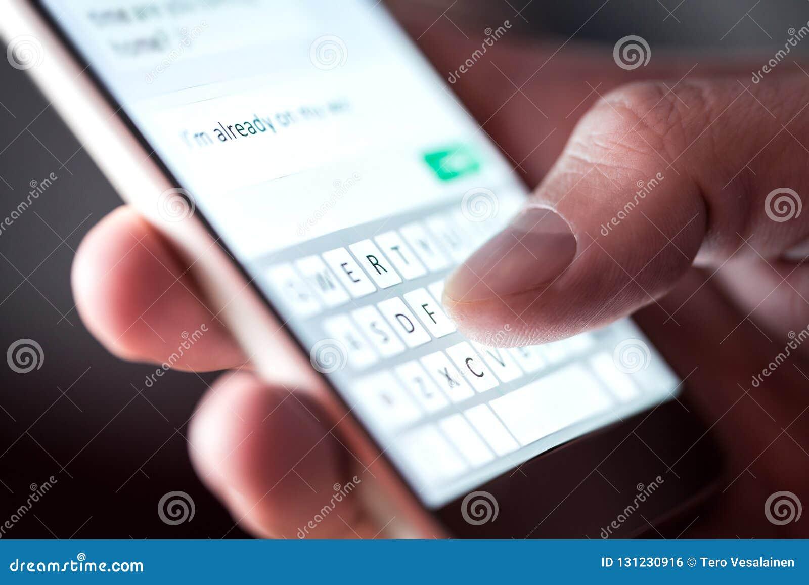 Homem que envia a mensagem de texto e os sms com smartphone Indivíduo que texting e que usa o telefone celular tarde na noite na