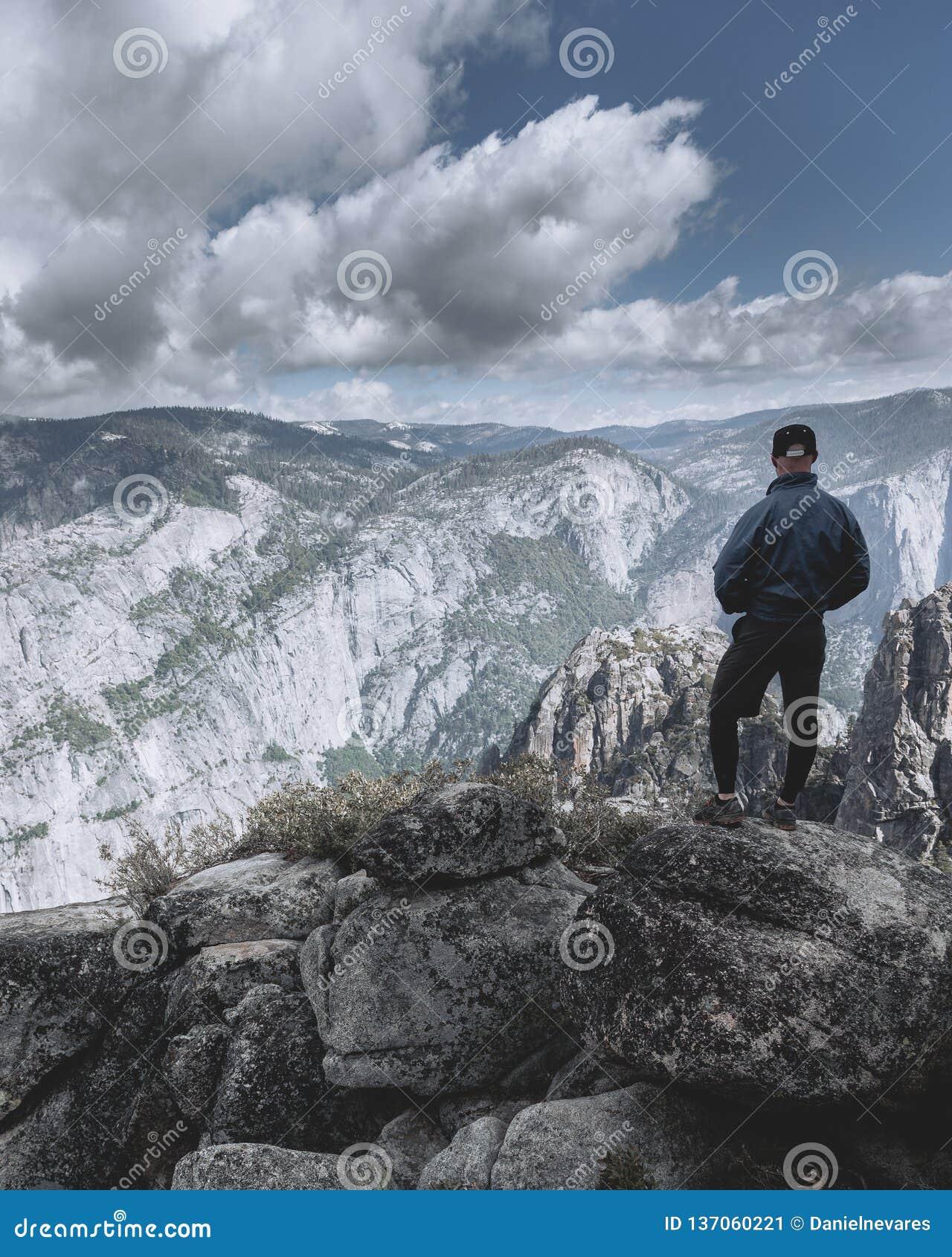 Homem que está apenas e que olha para fora em montanhas, em nuvens e no vale no parque nacional de Yosemite