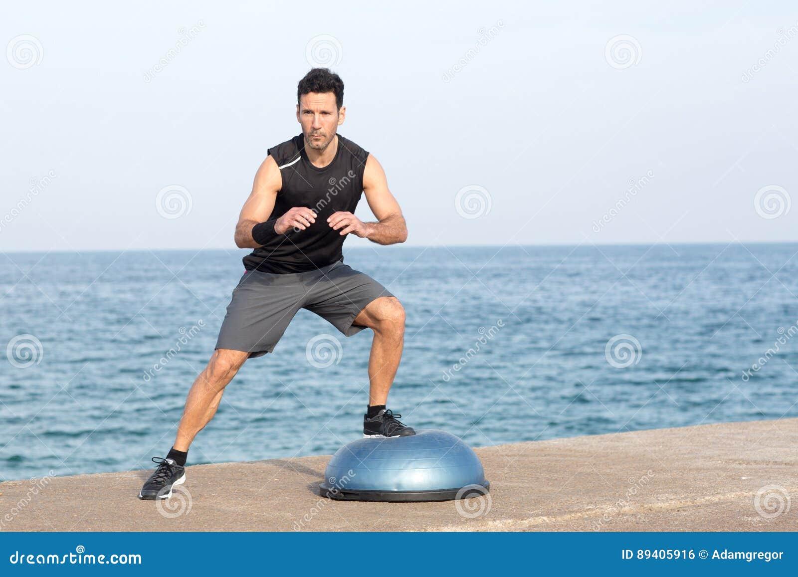 Homem que exercita na plataforma do equilíbrio