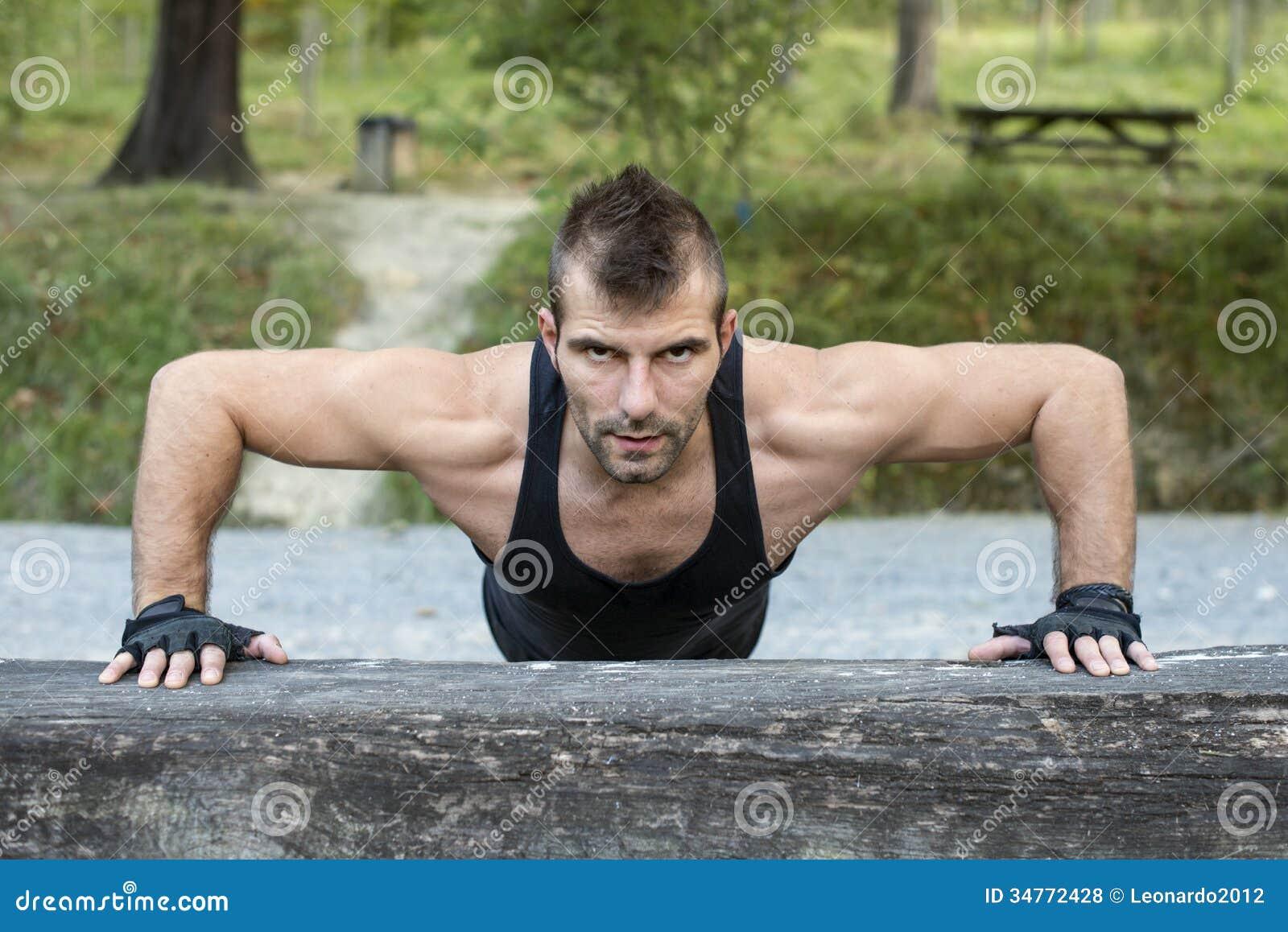 Homem que faz flexões de braço no log de madeira.