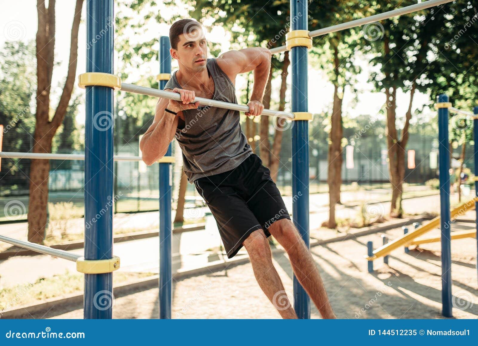 Homem que faz o exercício na barra horizontal exterior