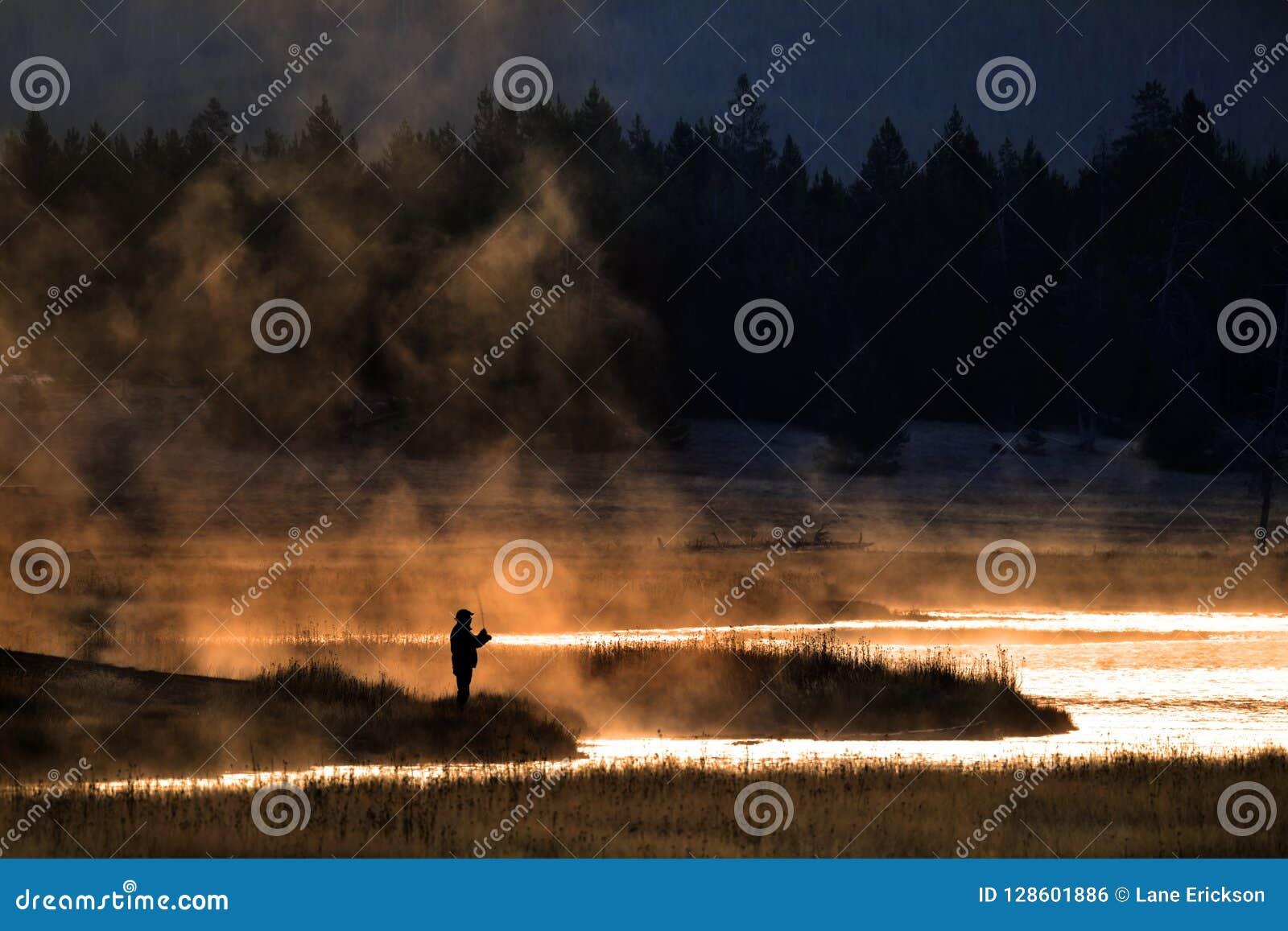 Homem que Flyfishing na névoa da luz do amanhecer do rio Sun dourado