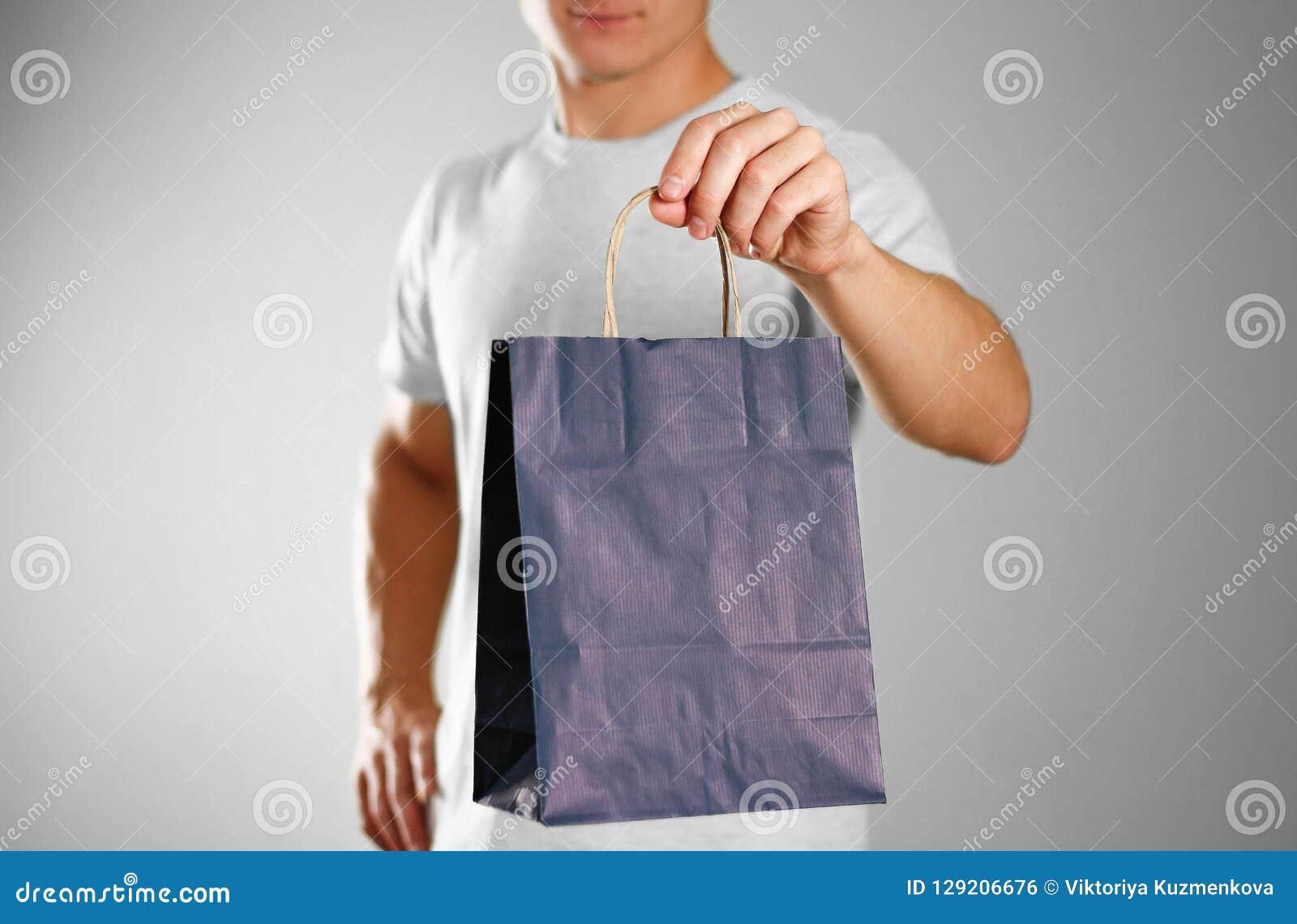 Homem que guarda um saco azul do presente Fim acima Fundo isolado