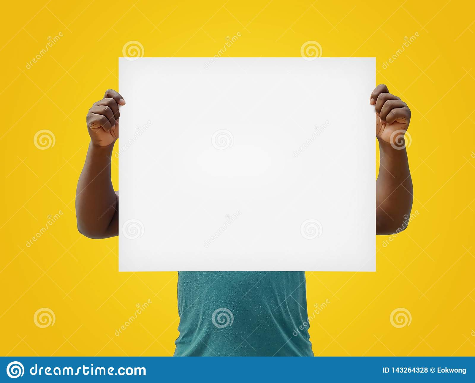 Homem que guarda um sinal vazio do branco sobre sua cara, isolada em um fundo amarelo