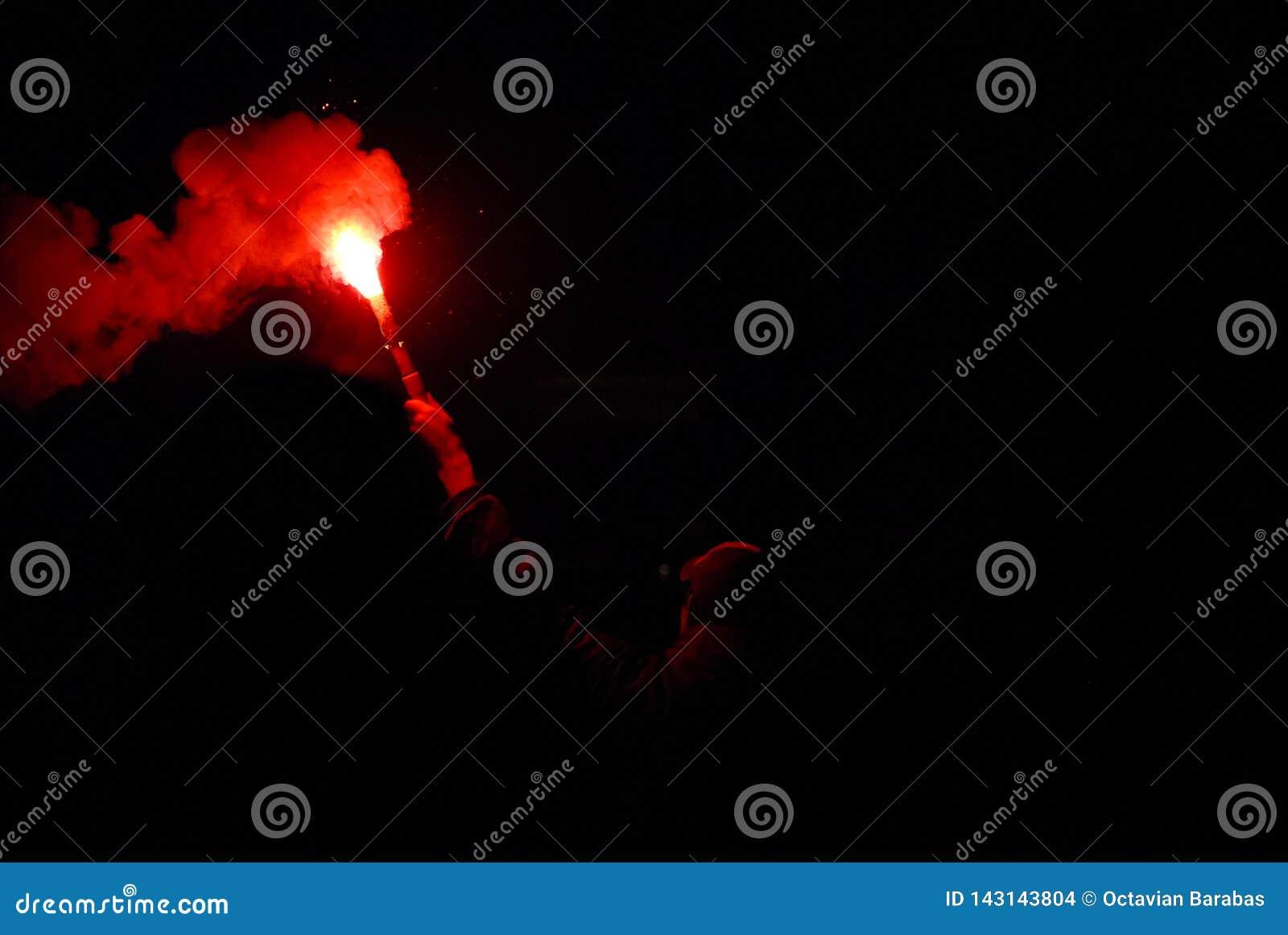 Homem que guarda uma vara vermelha ardente da fogueira