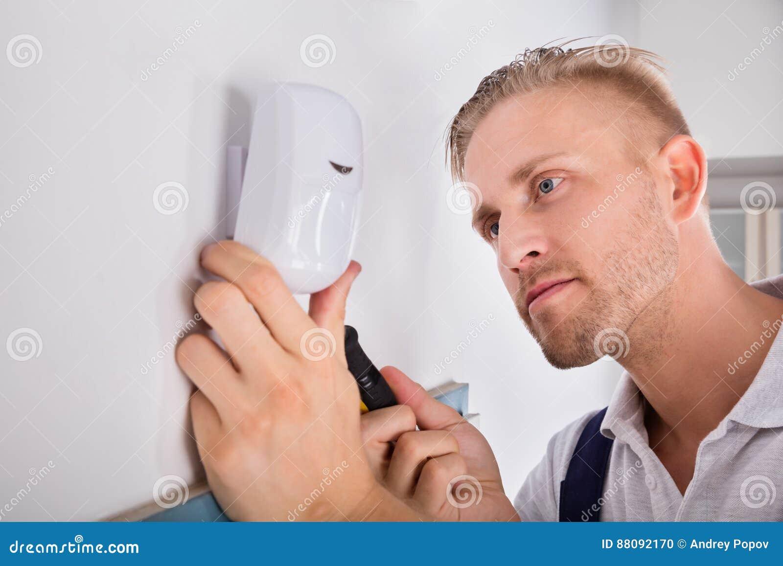 Homem que instala o detector de movimento para o sistema de segurança