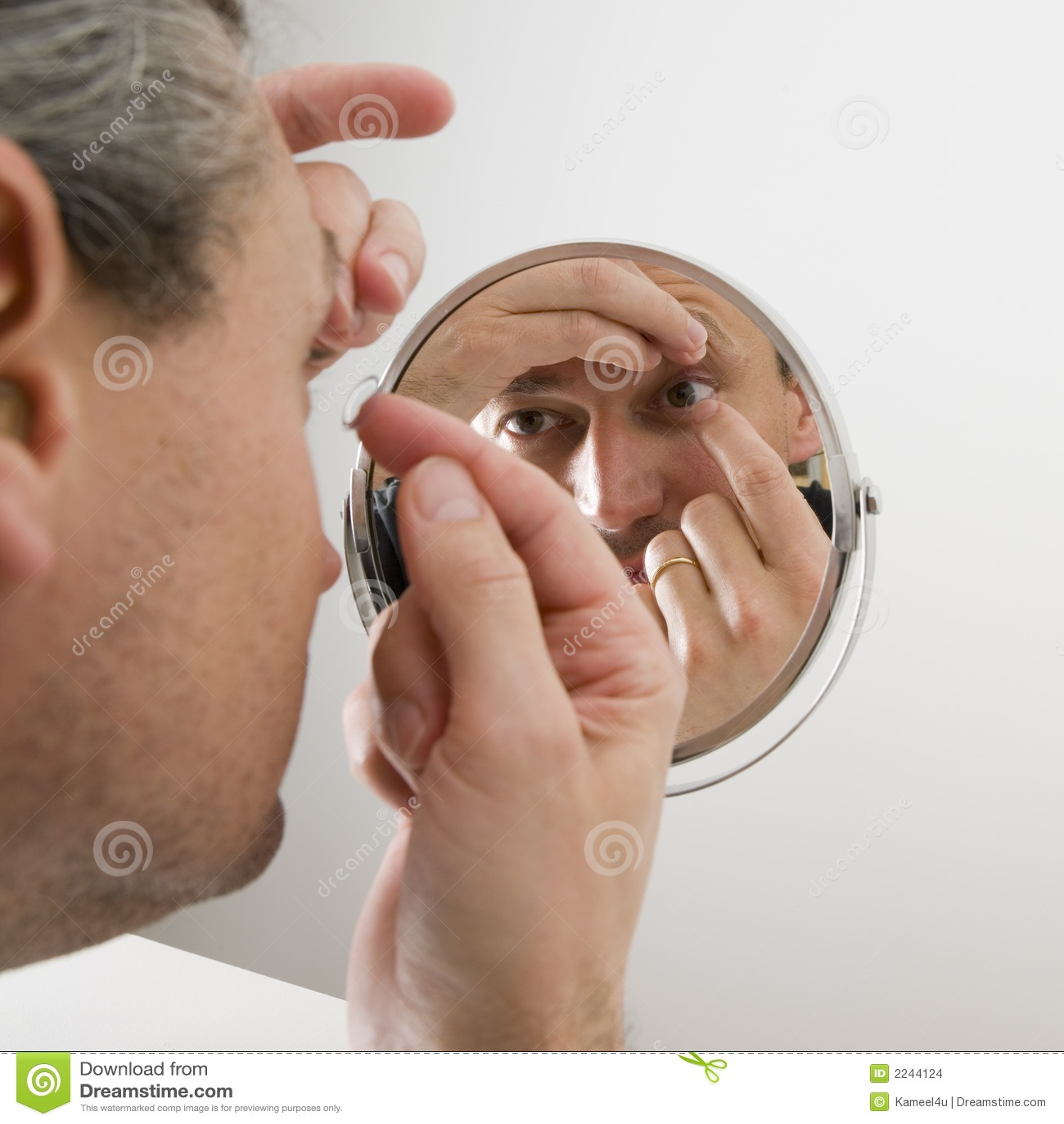 Homem que introduz uma lente de contato