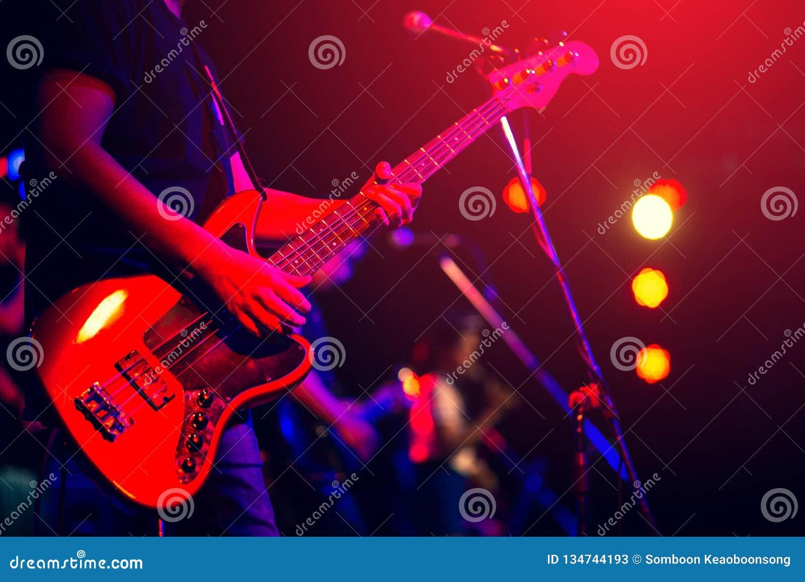 Homem que joga a guitarra baixa
