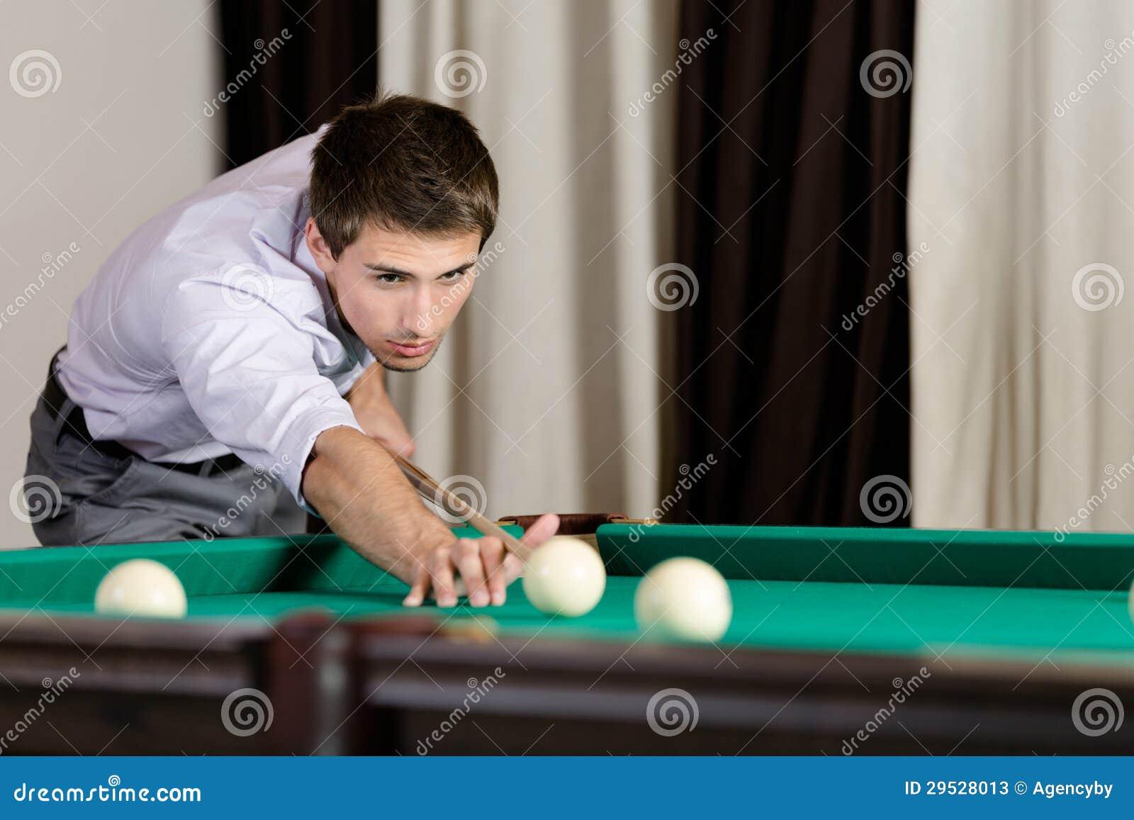 Homem que joga o bilhar na casa de jogo