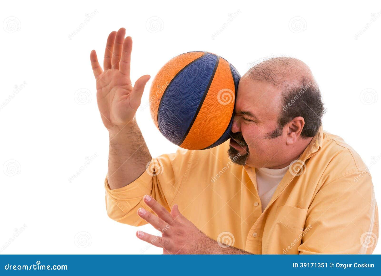 Homem que joga o esporte que está sendo batido por uma bola da cesta