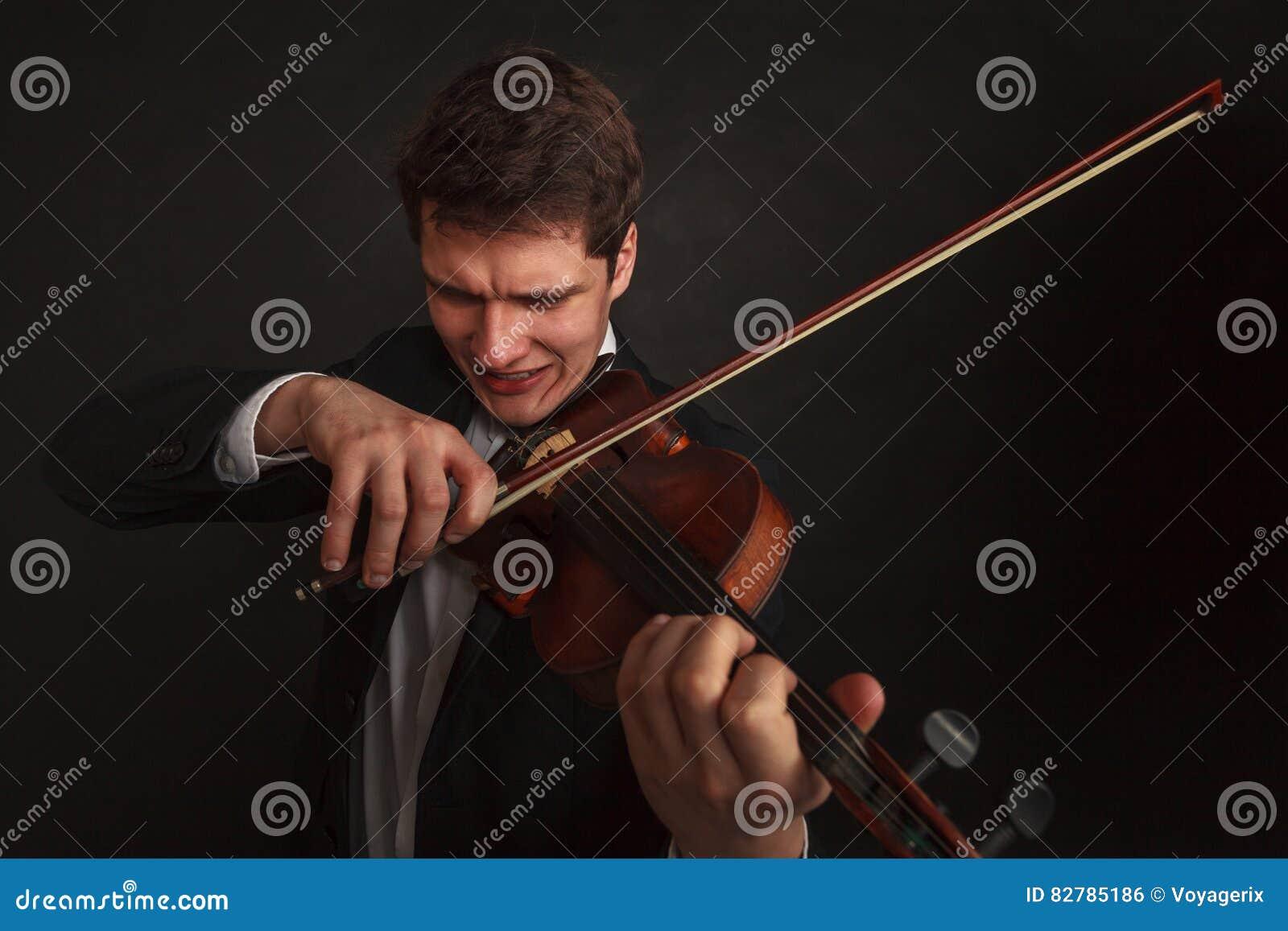 Homem que joga o violino que mostra emoções e expressões