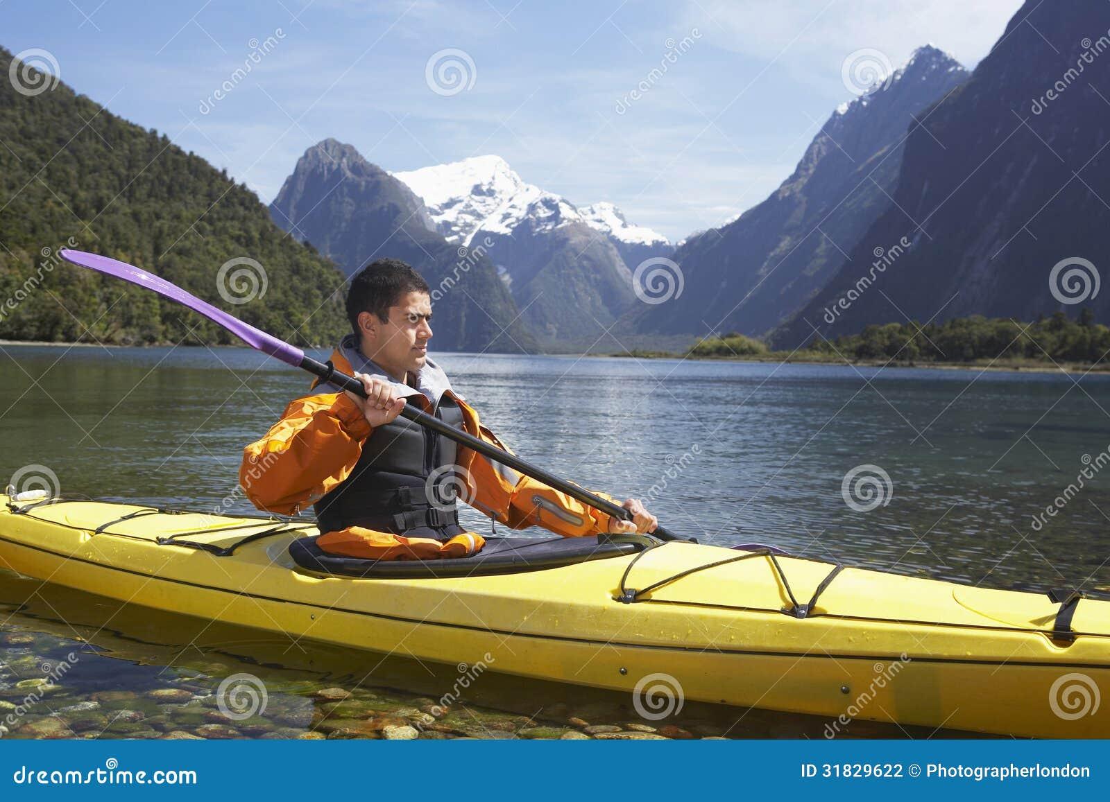 Homem que Kayaking no lago mountain