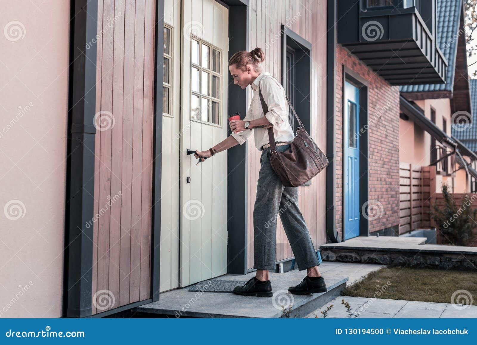 Homem que leva seus saco de couro e café marrons que voltam em casa
