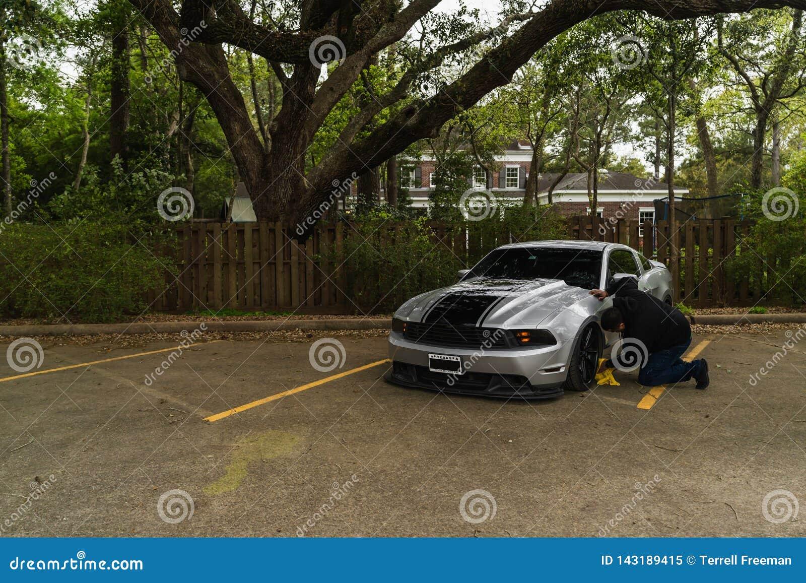 Homem que limpa Ford Mustang de prata