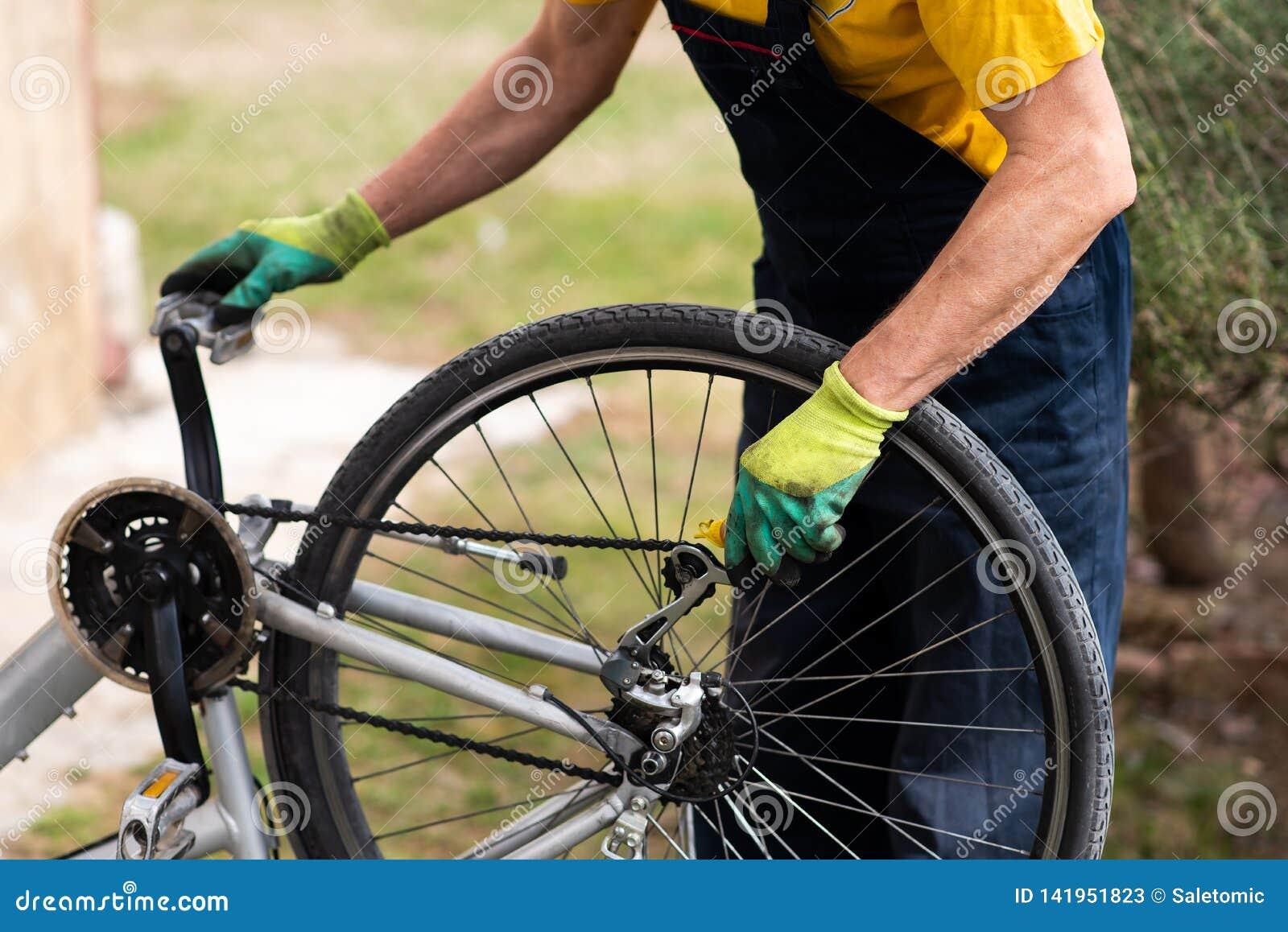 Homem que lubrifica a corrente da bicicleta que mantém para a estação nova