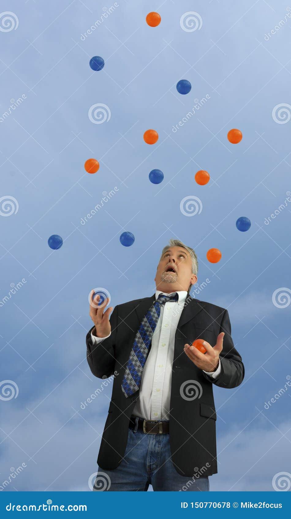 Homem que manipula muitas bolas no ar que representa sendo fora do controle ocupado na vida e no negócio com diversas coisas fati