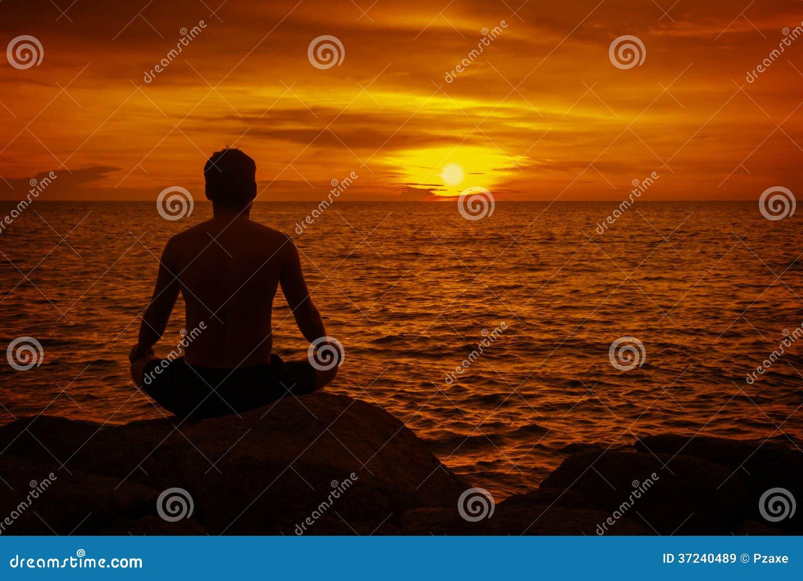 Homem que medita no por do sol. Praia tropical de Thaila