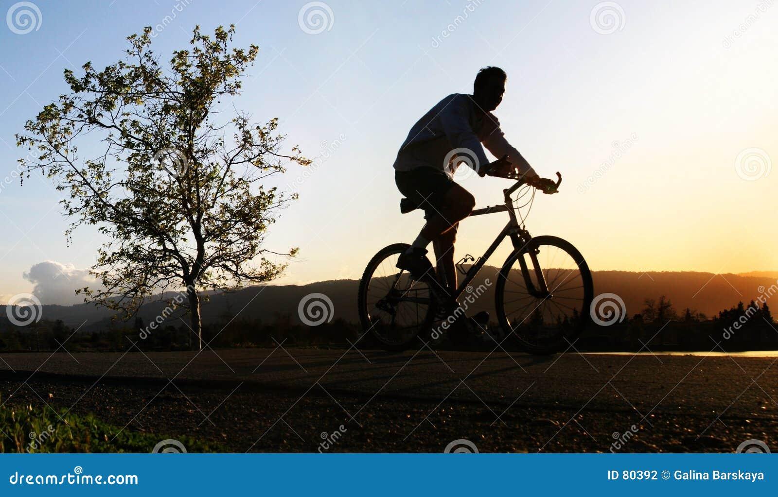Homem que monta sua bicicleta