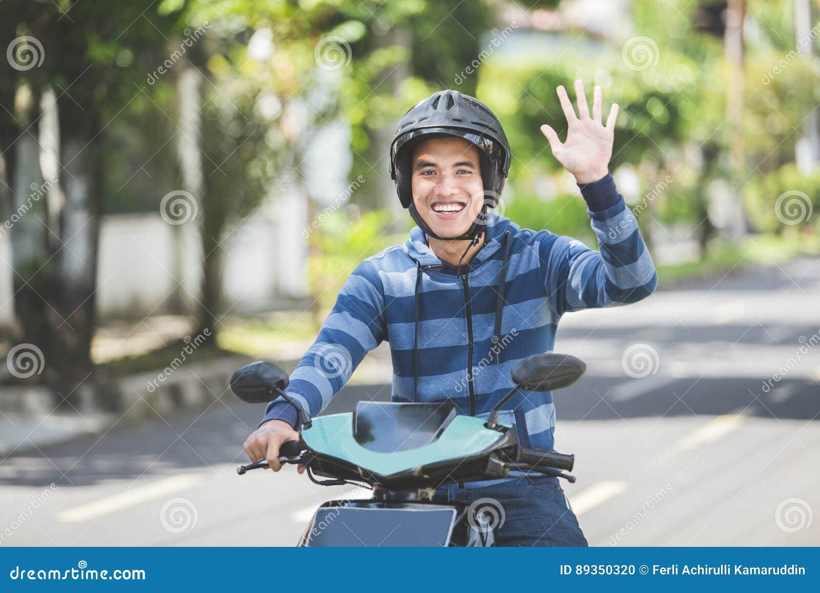 Homem que monta um velomotor e que acena a mão