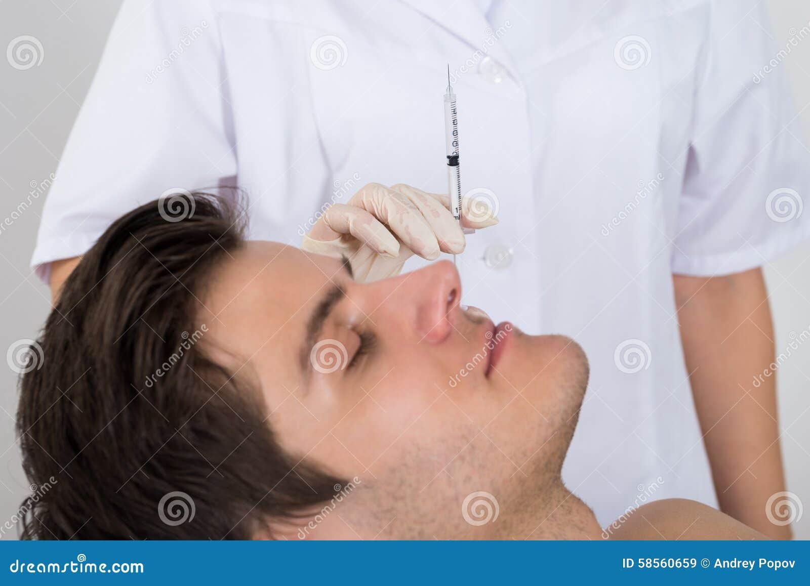 Homem que obtém o tratamento do enrugamento do doutor