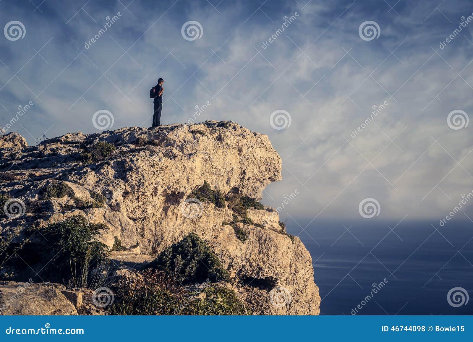 Homem que olha o horizonte de uma rocha