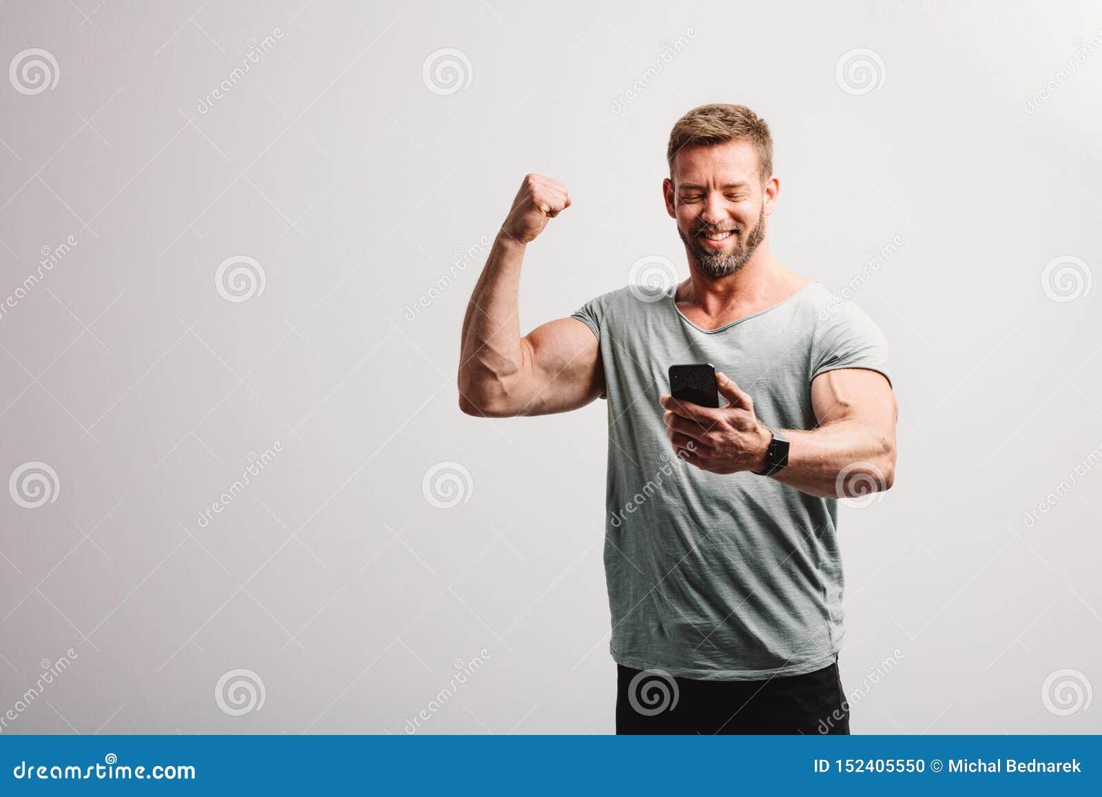 Homem que olha o smartphone com gesto de vencimento