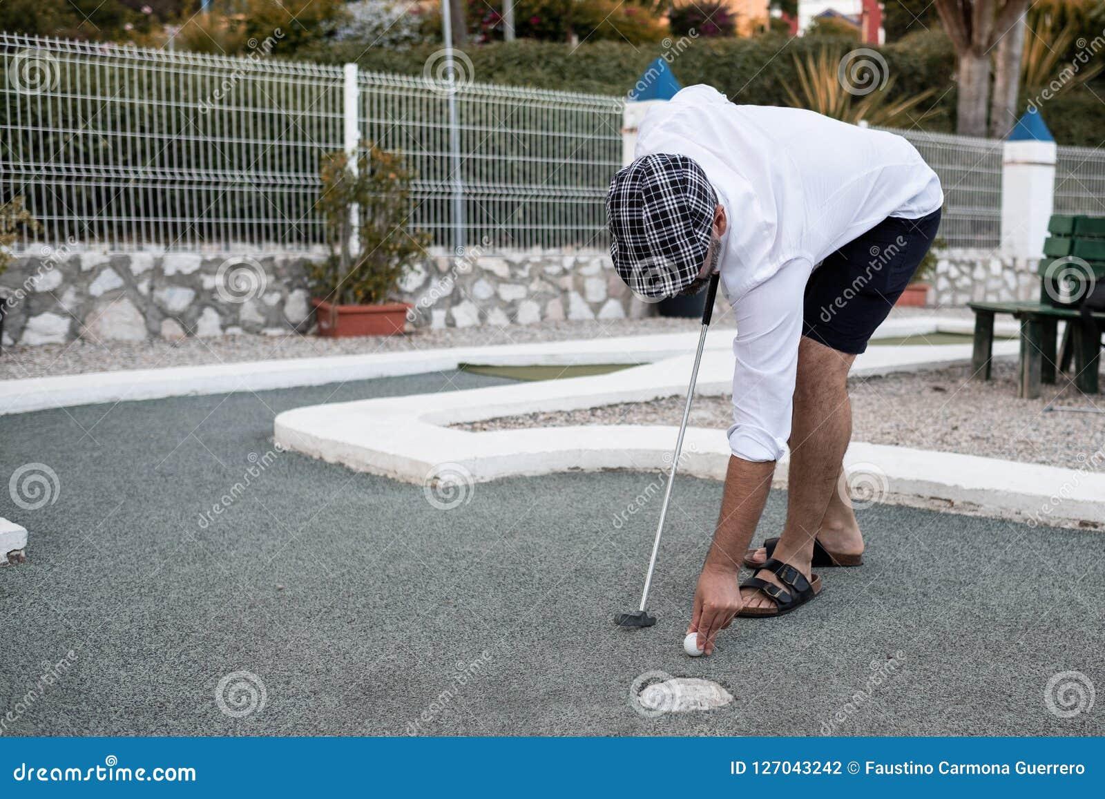 Homem que põe a bola de golfe ao lance