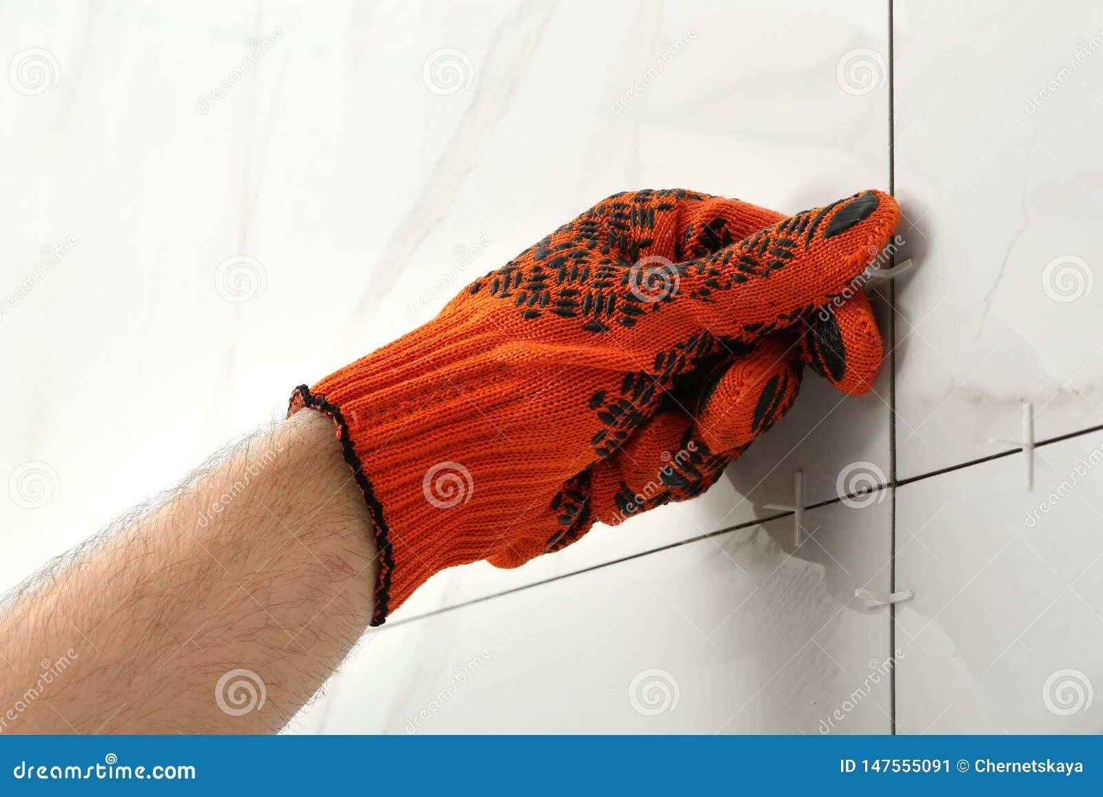 Homem que põe a cruz plástica na junção entre azulejos sobre a parede Trabalhos da constru??o e de renova??o
