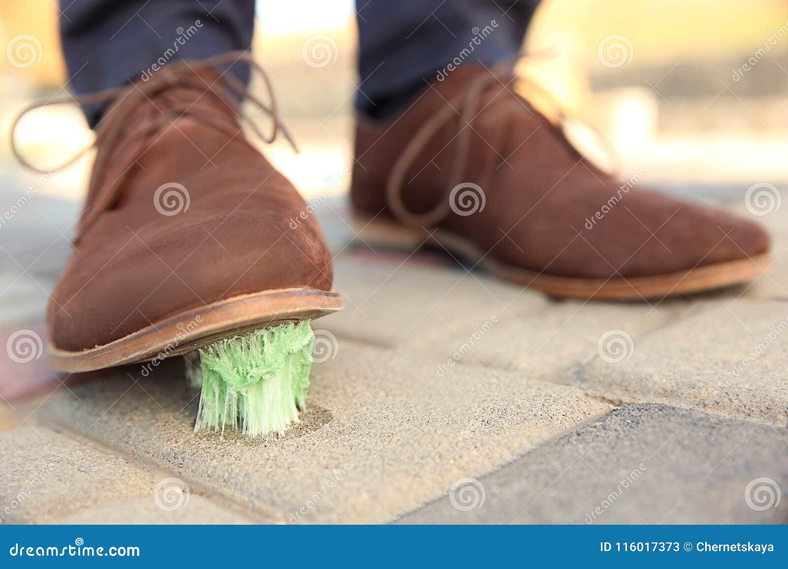 Homem que pisa na pastilha elástica no passeio