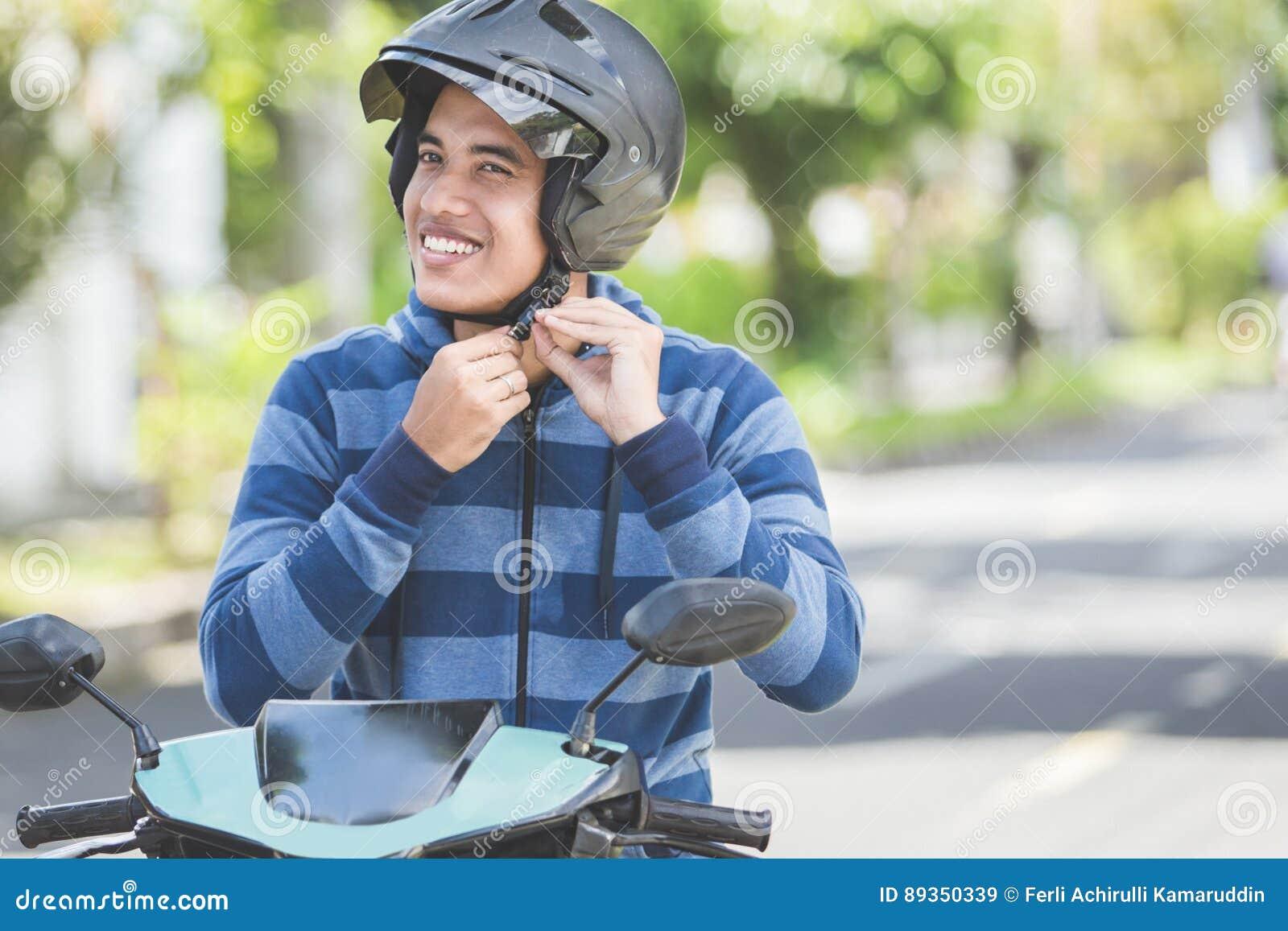 Homem que prende seu capacete do velomotor