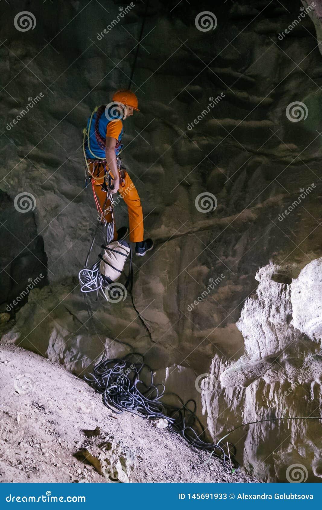 Homem que rappelling na caverna