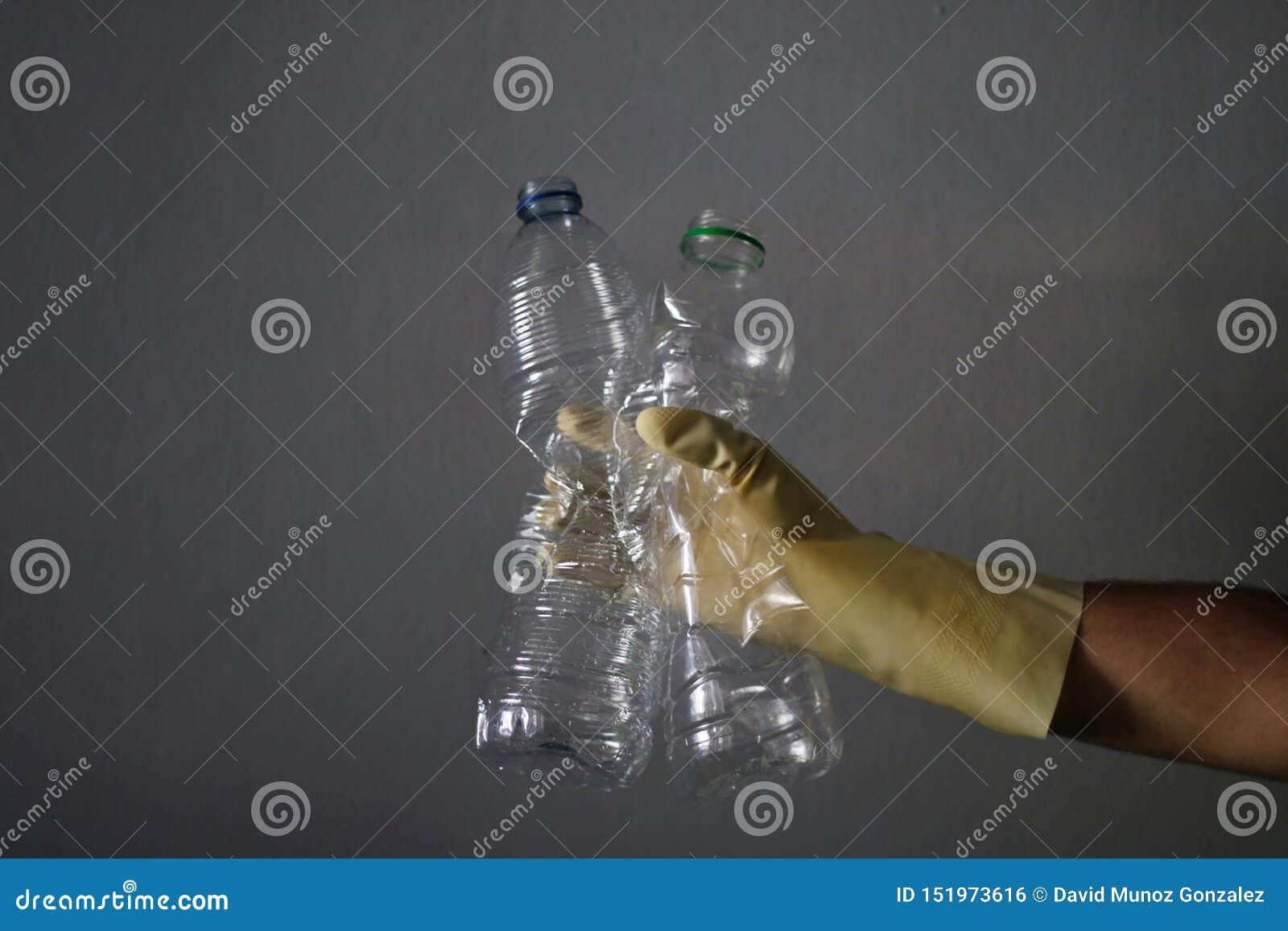 Homem que recicla algumas garrafas plásticas