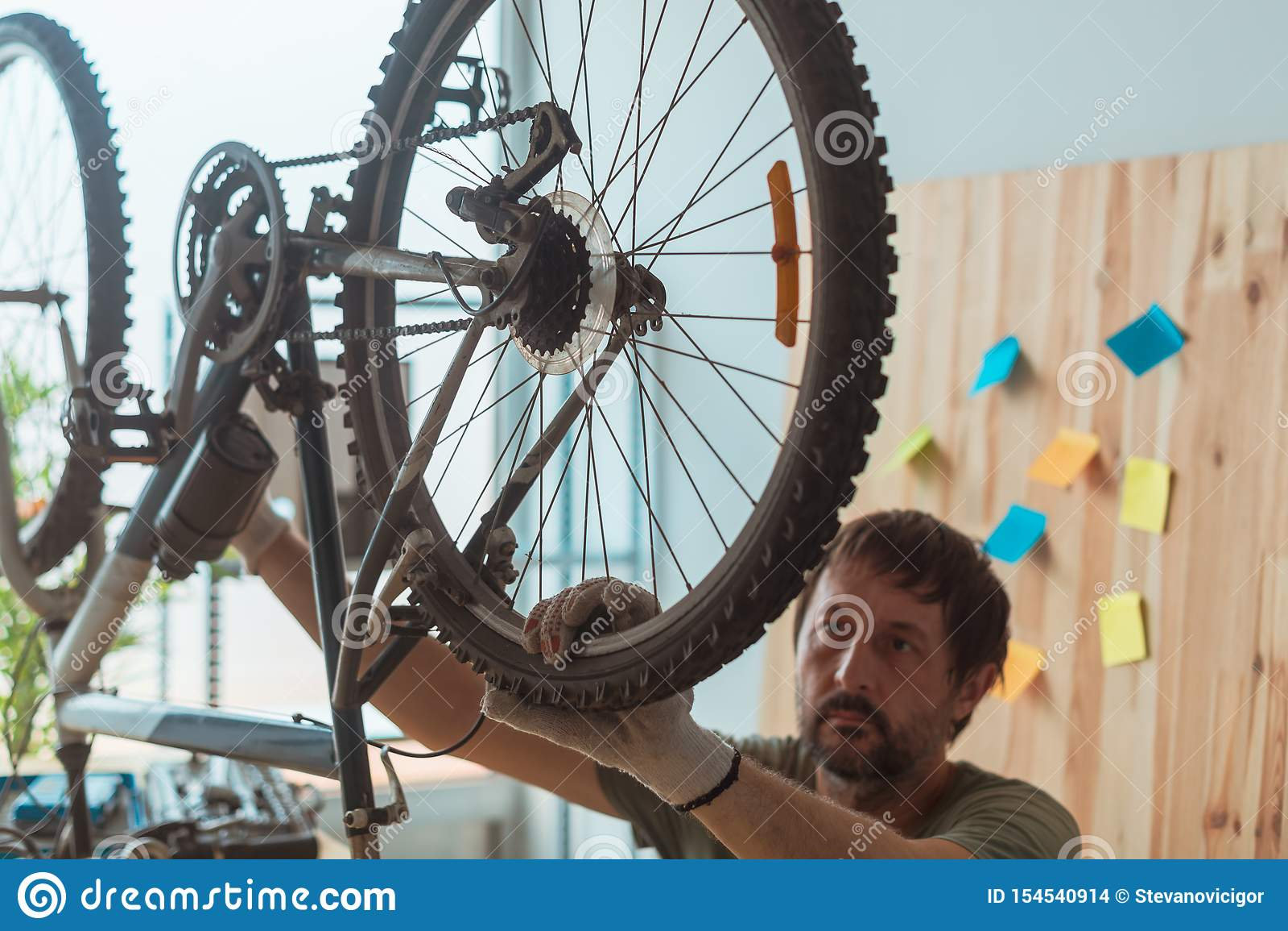Homem que repara o Mountain bike velho na oficina