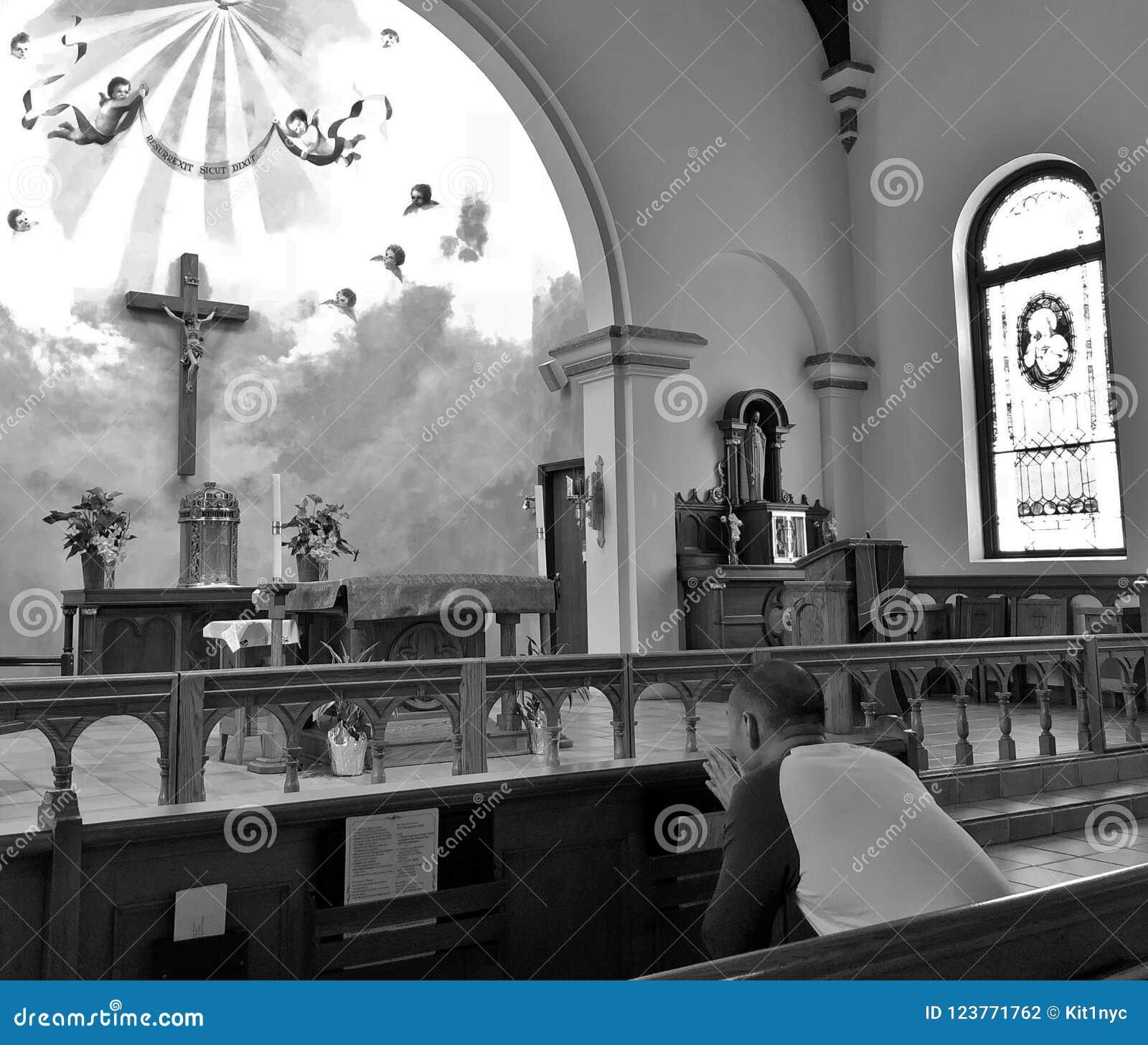 Homem que reza dentro de uma igreja religiosa com vitral e cruz bonitos