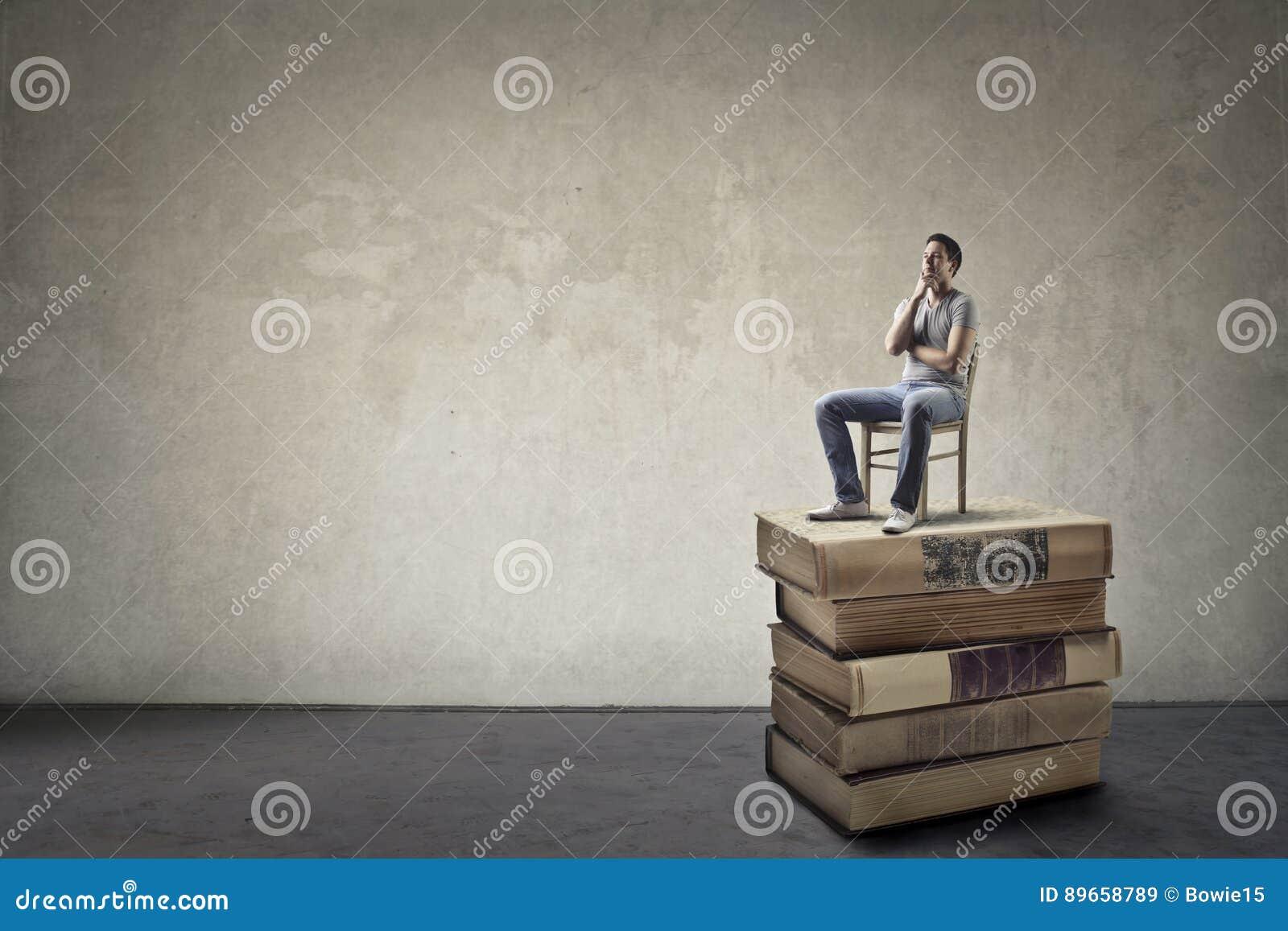 Homem que senta-se em livros