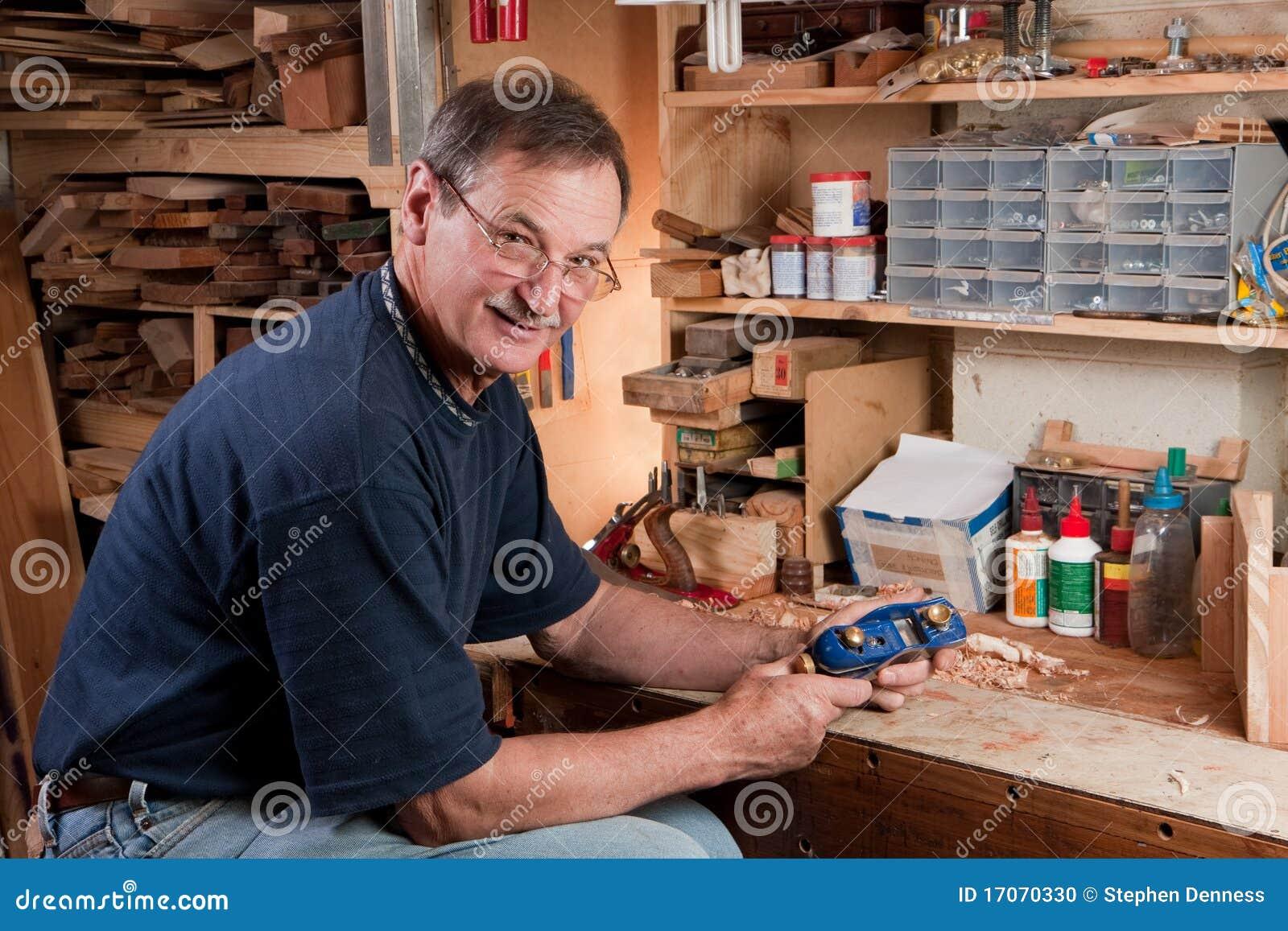 Homem Que Senta se Na Bancada Na Oficina Foto de Stock Imagem  #985D33 1300x957